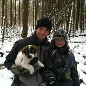 Stephen and his son pose with Cody on a winter hike.
